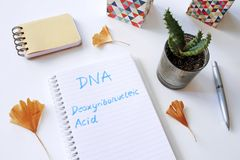 DNA Deoxyribonucleic Acid written in notebook. On white table royalty free stock photography