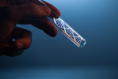 DNA molecule in glass tube in hand of scientist Stock Images