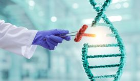 DNA molecules design with doctor hand holding pincers. Mixed media. DNA molecules with doctor hand in gloves holding pincers. Mixed media royalty free stock images