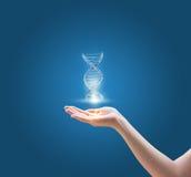 DNA-Moleküle in der Hand auf blauem Hintergrund Lizenzfreie Stockfotos