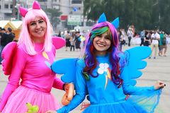 Two funny young girls  in blue and pink bright carnival dresses are smiling and walking along the street at the festival in Dnepr. Dnepr city, 5 09 2019. Two stock photos