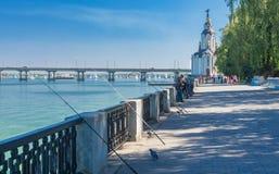 Dnepr river embankment with fishermen and their rods. DNEPR, UKRAINE - SEPTEMBER 10, 2016:Dnepr river embankment with fishermen and their rods during City Day royalty free stock photos