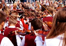 Playing the violin at a carnival procession in honor of celebrating the city`s day. stock image