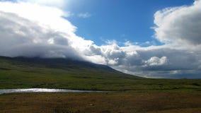 Dnia słońca promienie przebijali gęstego chmura która ściska górę, posypują z zielonymi trawami i dekorują z górą zdjęcie royalty free