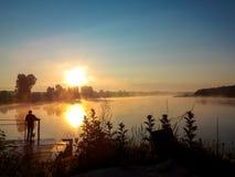 Dnieje na jeziorze sylwetkę mężczyzna na moscie niezapomniany krajobraz Zdjęcia Royalty Free