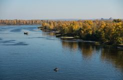 River, blue sky and forest. Picturesque sunny autumn landscape. Dnieper River, Ukraine, Eastern Europe. River and autumn forest. Picturesque colorful autumn royalty free stock photography