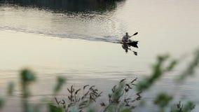 Dniepropetovsk, Ukraine - 7 mai 2017 : équipez le canotage avec le canoë sur la rivière au coucher du soleil à Dniepropetovsk, Uk banque de vidéos