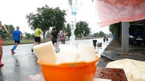 DNIPRO, ΟΥΚΡΑΝΊΑ 20 ΜΑΐΟΥ: Ο εθελοντής χύνει το νερό στα washcloths για να αναζωογονήσει τους δρομείς στο μαραθώνιο σε 3$ο INTERP φιλμ μικρού μήκους