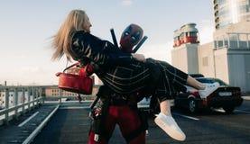 DNIPRO UKRAINA - MARS 28, 2019: Deadpool cosplayer har gyckel och bär flickan på hans händer arkivfoto