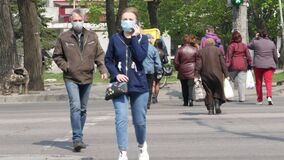 People walk along city street and wear face masks and latex gloves. Quarantine