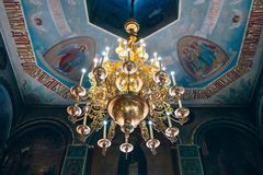 Church of St. Nicholas, large gold or bronze chandelier in the temple or cathedral Stock Photos