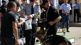 Dnipro, Ukraine- August 7, 2018: policeman give winner`s cup to cop and put on gold medal to him and k9 german shepherd. Dog at 3d national championship of stock video