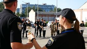 DNIPRO, UKRAINE- AUGUST 7, 2018: policeman give winner`s cup to cop and put on gold medal to him and k9 german shepherd. Dog at 3d national championship of stock footage