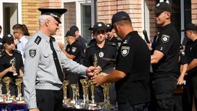 DNIPRO, UKRAINE- AUGUST 7, 2018: policeman give winner`s cup to cop and put on gold medal to him and k9 german shepherd. Dog at 3d national championship of stock video footage