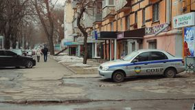 A security vehicle with a SOBR guard is parked at the entrance to a dry-cleaner. A man and woman are walking down the street hold. DNIPRO, UKRAINE - FEBRUARY 11 stock video footage