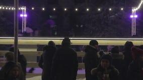 DNIPRO, UKRAINE - 6. Januar 2019: Leute stehen und gehen um den Zaun der Eisbahn und betrachten die Eislaufeisschlittschuhläufer stock video footage