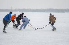 Group of different aged people playing hokey on a frozen river Dnipro in Ukraine. Dnipro, Ukraine - January 28, 2018: Group of different aged people playing royalty free stock image