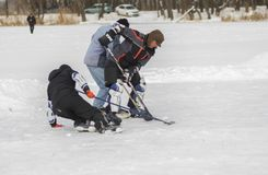 Three mature amateur men fighting for the puck while playing hockey on a frozen river Dnepr in Ukraine. Dnipro, Ukraine - January 27, 2018: Three mature amateur stock images