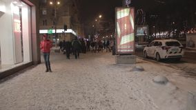 DNIPRO, UKRAINE - 6 JANVIER 2019 : Les gens marchent le long de la rue lumineuse près des fenêtres de magasin Voiture de police a clips vidéos