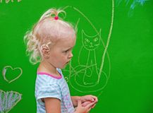 Girl draws with chalk. Dnipro, Ukraine - June 27, 2018: Little girl draws funny scribbles on the day of putting into operation an inclusive city park royalty free stock image