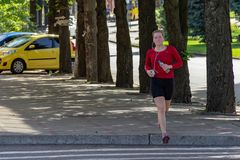 DNIPRO, UKRAINE - June 16, 2019: Young girl goes for sports on street. Wellness jogging. Woman in red T-shirt sneakers and black. Sports tights runs along stock photos