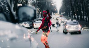 DNIPRO, UKRAINE - MARCH 28, 2019: Deadpool cosplayer crossing the city street with guns and katanas royalty free stock photos