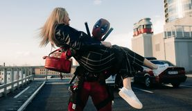 DNIPRO, UKRAINE - MARCH 28, 2019: Deadpool cosplayer has fun and carries girl on his hands stock photo