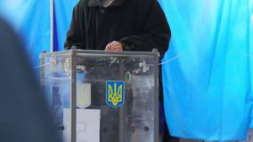 An elderly male voter puts the electoral ballot in the ballot box. Election of the President of Ukraine. Coat of arms an emblem. Dnipro, Ukraine - March 31, 2019 stock video footage
