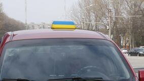 Private taxi car with yellow-blue sign in colors of national flag is waiting