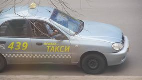 Private taxi driver resting in his parked car with mobile phone in hand. Most orders are received from the dispatcher. Dnipro, Ukraine - March 27, 2019: Private stock video footage