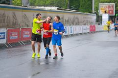 Participants helping other guy who is loosing consciousness during of the `Interipe Dnipro Half Marathonrace`. DNIPRO, UKRAINE - MAY 20, 2017: Friendly stock photography