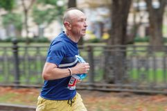 Senior man running on a city street during 21 km distance of ATB Dnipro Marathon stock images