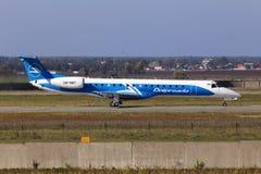Dniproavia巴西航空工业公司ERJ-145航空器为从跑道的起飞做准备 库存图片