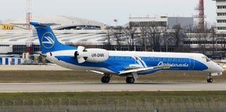 Dniproavia巴西航空工业公司ERJ-145在跑道的航行器着陆 免版税库存图片