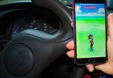 Dnipropetrovsk, Ucrania - 23 de julio de 2016: La mano femenina que sostiene el teléfono con el juego Pokemon ENTRA en el coche Foto de archivo libre de regalías