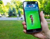 Dnipropetrovsk, Ucrania - 23 de julio de 2016: La mano femenina que sostiene el teléfono con el juego Pokemon ENTRA en parque Imágenes de archivo libres de regalías
