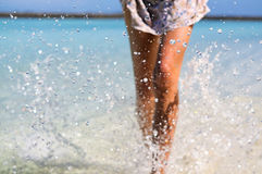 Dünne bräunende Frauenbeine, die Wasser spritzen lassen Ferien- und Sommerstimmung Lizenzfreies Stockbild