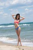 Dünner Mädchenabnutzungsbikini, Strand mit wilden Wellen Stockfoto