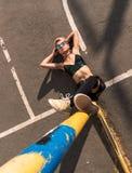 Dno strzał Uliczna punkowa dziewczyna z menchia farbującym włosy Siedzi na Żelaznej tubce na asfaltowym tle Kobieta z przebijanie zdjęcia stock