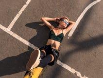 Dno strzał Uliczna punkowa dziewczyna z menchia farbującym włosy Siedzi na Żelaznej tubce na asfaltowym tle Kobieta z przebijanie fotografia royalty free