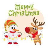 Dnowman in hat and mittens with Christmas reindeer in scarf Royalty Free Stock Photography