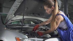 Doświadczony mechanika przędzalnictwo z pomocą narzędzia silnik od auto mechanika naprawia samochód w rozkazie dla zdjęcie wideo