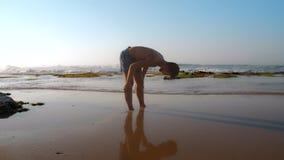 Doświadczeni atleta stojaki w mokrym piasku odbija sylwetkę zbiory wideo