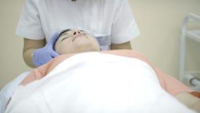 Doświadczona lekarka egzamininuje twarz kłama indoors kobieta zdjęcie wideo