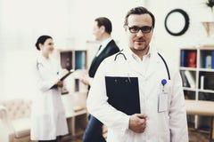 Doświadczona lekarka z stetoskopem stoi z falcówką dokumenty Rekonwalescenci pojęcie obraz stock