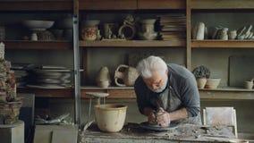 Doświadczonego rzeźbiarza starszy dorosły robi rzeźbie od glinianej piłki na miotaniu toczyć Nawadnia glinę łagodzić je zdjęcie wideo