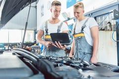 Doświadczony auto mechanik używa laptop dla skanować parowozowych błędów kody Fotografia Stock
