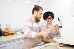Doświadczony barista uczy nowego pracownika używa kawy espresso machina zdjęcie stock