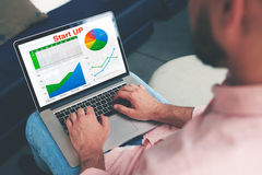 Doświadczony biznesmen patrzeje pieniężnych dane z grafika i mapami podczas gdy praca na laptopie Zdjęcia Stock
