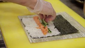 Doświadczony kucharz stawia ogórki na podstawie dla rolek w kuchni restauracja zdjęcie wideo